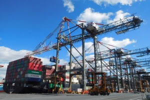 large cranes at a port with blue sky background