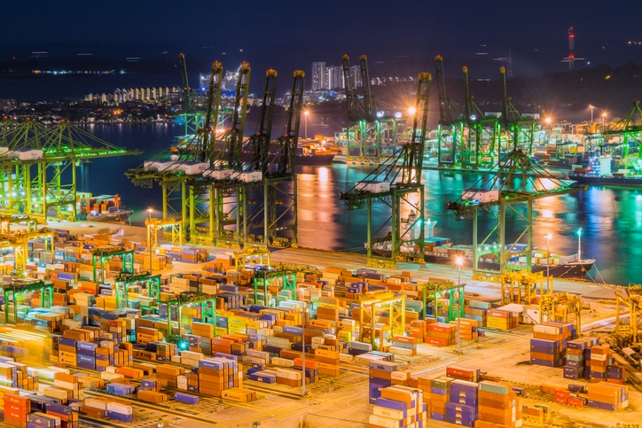 Ships docking at container terminal for loading and unloading of cargo during the night in Singapore port.