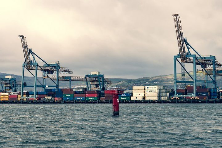 Belfast, United Kingdom: March 10, 2019:  Shipping containers stacked high at the container dock of Belfast Harbour, Northern Ireland.  As the proposed date for the UK's departure from the EU approaches (Brexit), manufacturers and retailers have stock piled goods at the port in shipping containers just in case the terms of Brexit disrupt supplies.  Cross-processed.