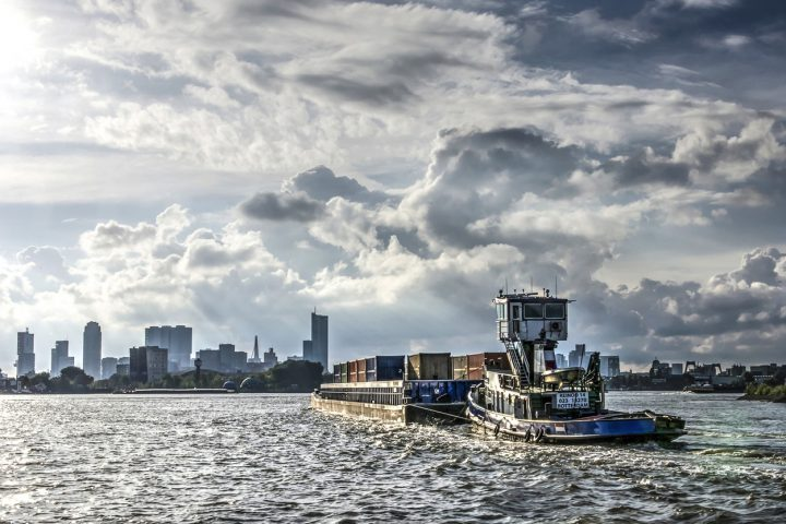 An inland barge loaded with containers on the Nieuwe Maas river approaching city and harbour of Rotterdam