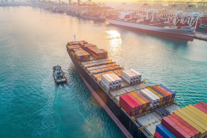 aerial view of containers ship vessel arrival approach to the main entrance gate od an international port, transport and logistics system services to worldwide global of seas and lands