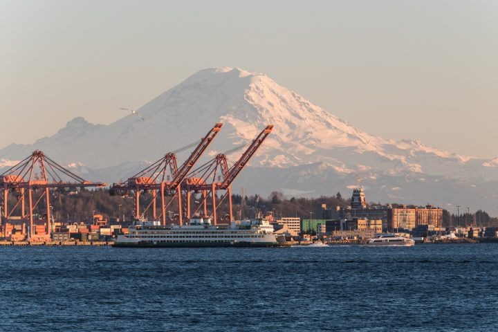 Seattle, USA - Mar 4, 2019: A ferry on Elliott bay late in the day with Mount Rainer and the ports in background.