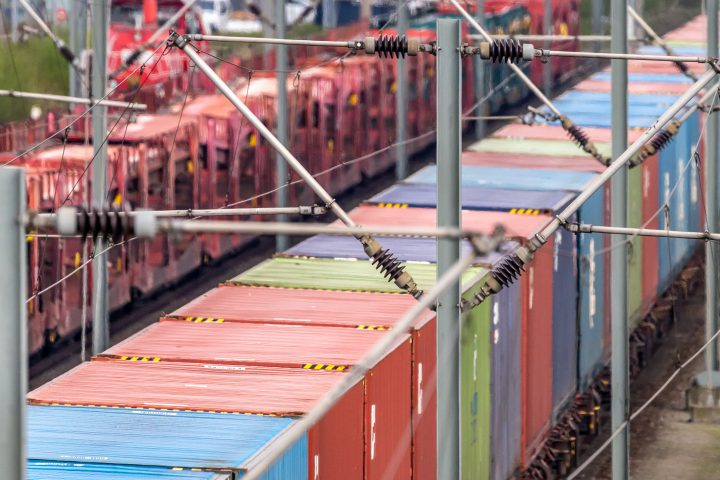 Telephoto recording of a freight wagon on the rails with coloured containers, abstract