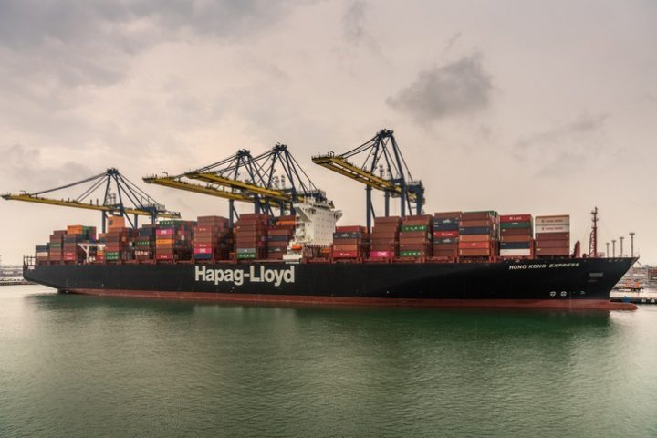 Laem Chabang, Thailand - March 16, 2019: Container port and terminal and Hapag Lloyd ship under gray sky. Four yellow cranes loading and unloading it. Colored container stacks on ship.