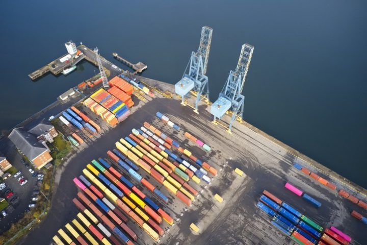 Containers and cranes at logistics port terminal with many colours aerial view from above uk