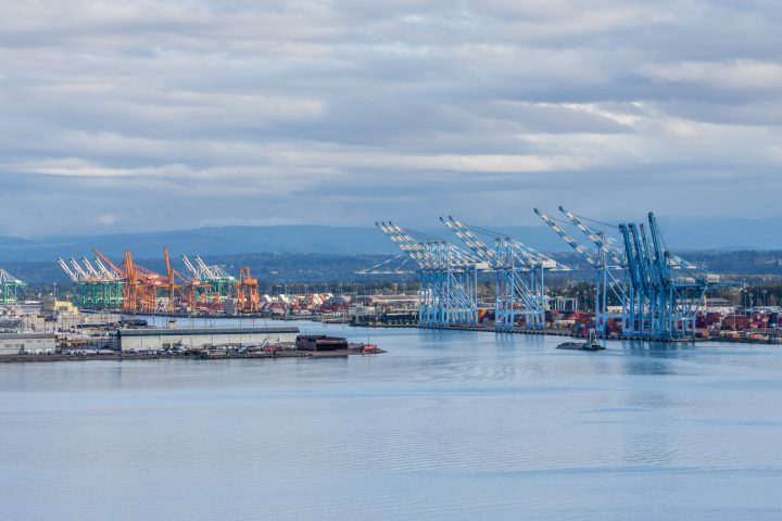 The wharf at the Port of Tacoma with many cranes for shipping.