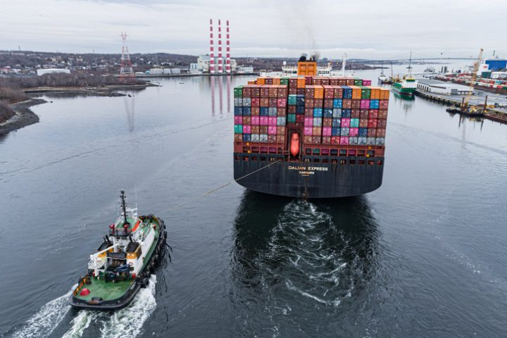 Halifax, Canada - December 2, 2020 - Assisted by a tugboat, the Dalian Express navigates narrow Halifax Harbour heading for another port.