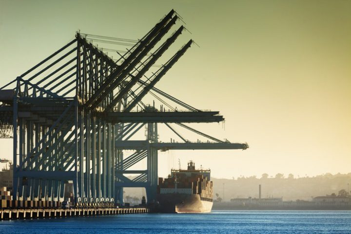 Large industrial container cranes load a cargo ship at the Port of Los Angeles