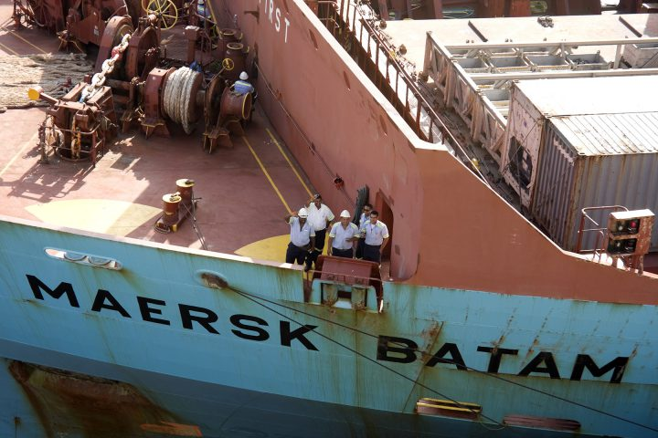 Panamá City, Panamá Province, Panamá - February 28, 2015: Aerial view of the bow of a load ship MAERSK BATAM. Five men in uniform, salute as the ship passes through the Miraflores Locks of the Panama Canal. Behind, marine rigging and containers.