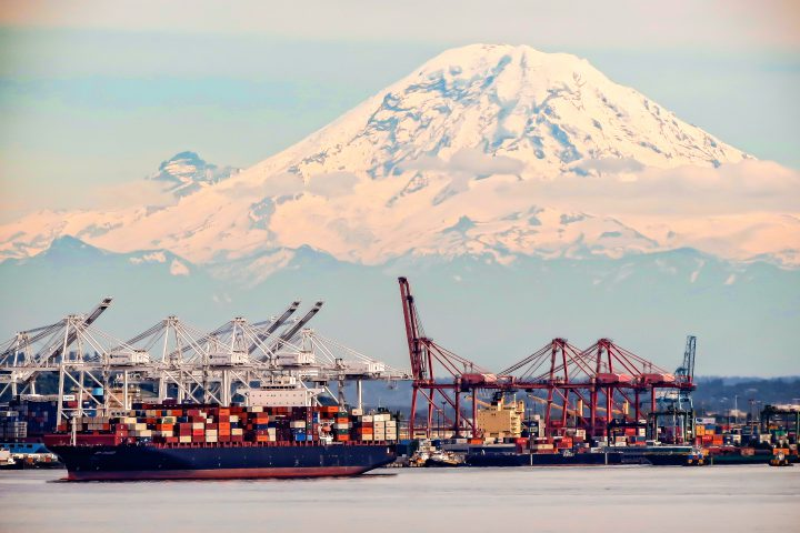 Seattle, Washington, USA- June 15, 2012:  Cranes and container ships make for a  busy shipping industry in the Port of Seattle inside Elliot Bay with a view of Mount Adams in the background.