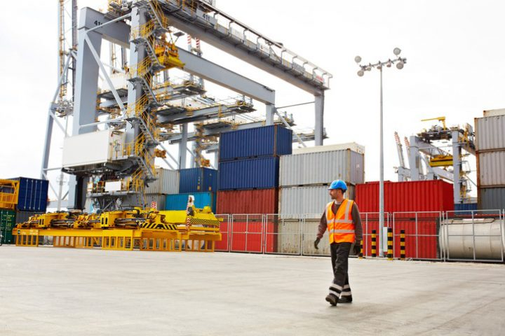 Shot of a young man in workwear walking outside on a large commercial dock