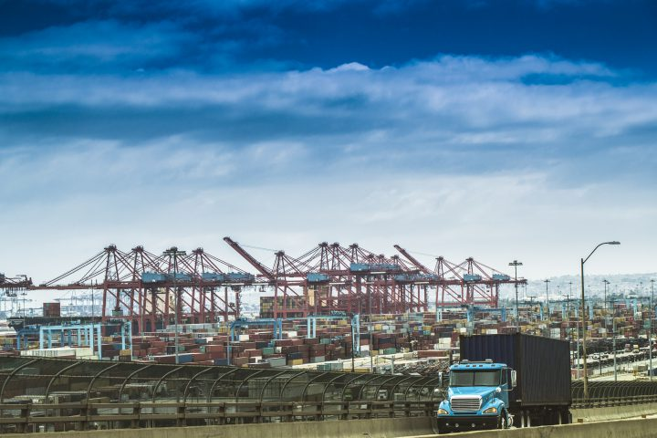 A stock photo of a Cargo Truck driving on the road with the Port of Los Angeles/Long Beach in the background. All logos removed. Photographed using the Canon EOS 1DX Mark II