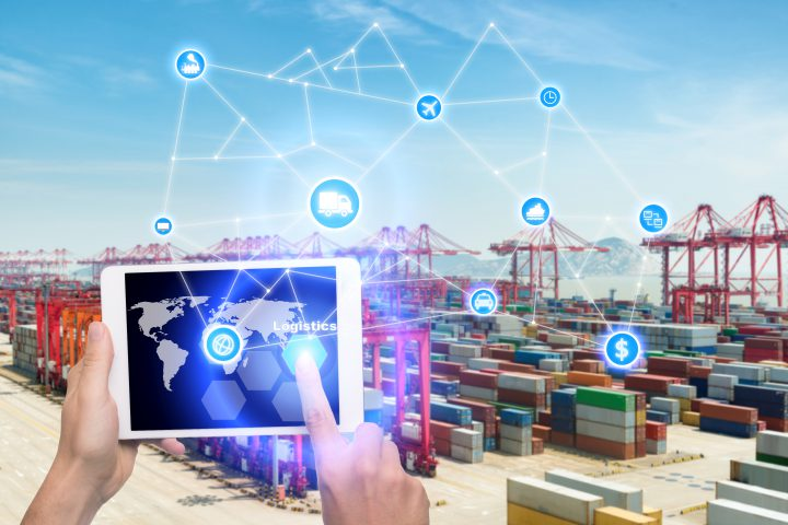 Hand holding tablet is pressing button Logistics connection technology interface global partner connection for logistic import export background. Business logistics concept , internet of things