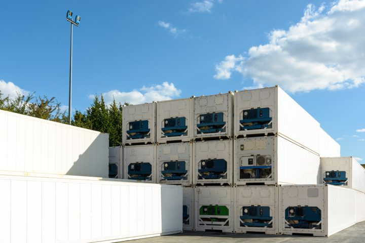 Dozens of immaculate white refrigerated containers stacked in the sunlight in a shipping yard in the region of Paris.
