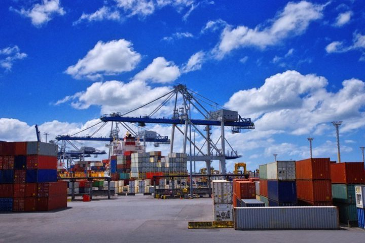 View of colorful containers and cargo cranes in the port. International cargo shipping concept.