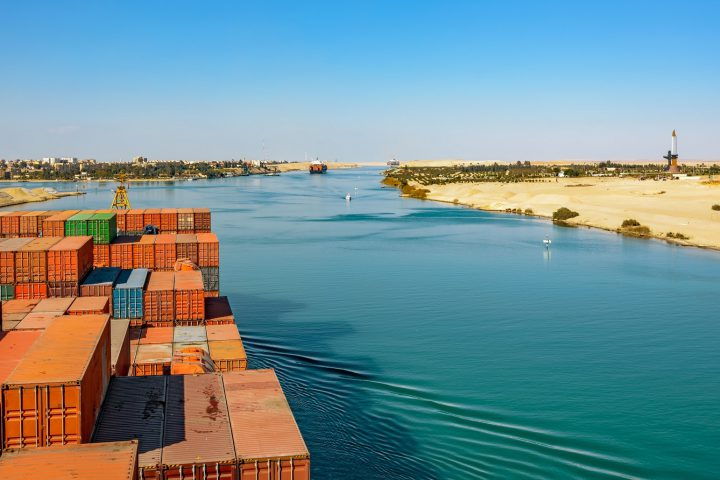 Industrial container ship passing through Suez Canal with ship's convoy, view on the bow from the captain bridge.